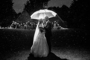 Bride and groom under umbrella