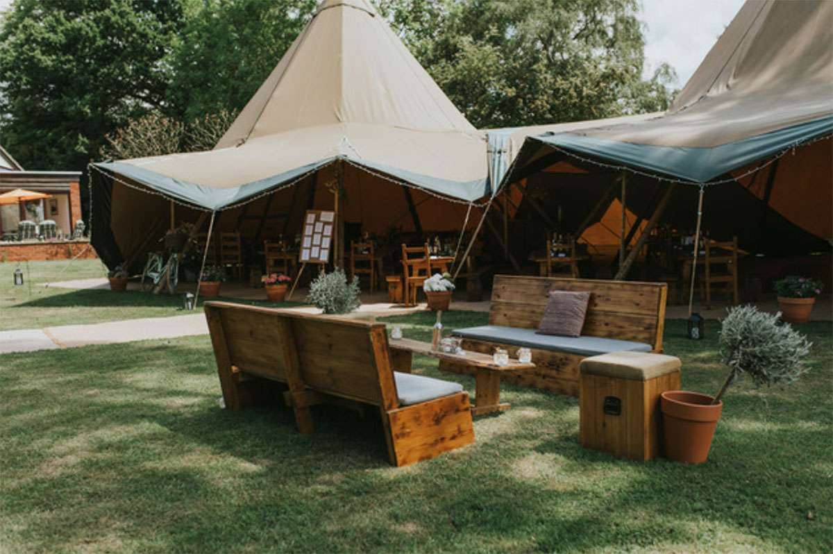 benches outside tipi on grass