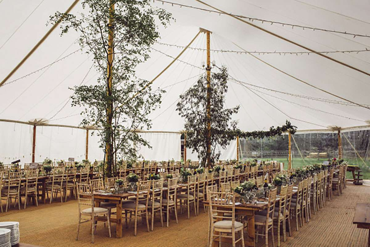 tables in chairs inside sailcloth tent