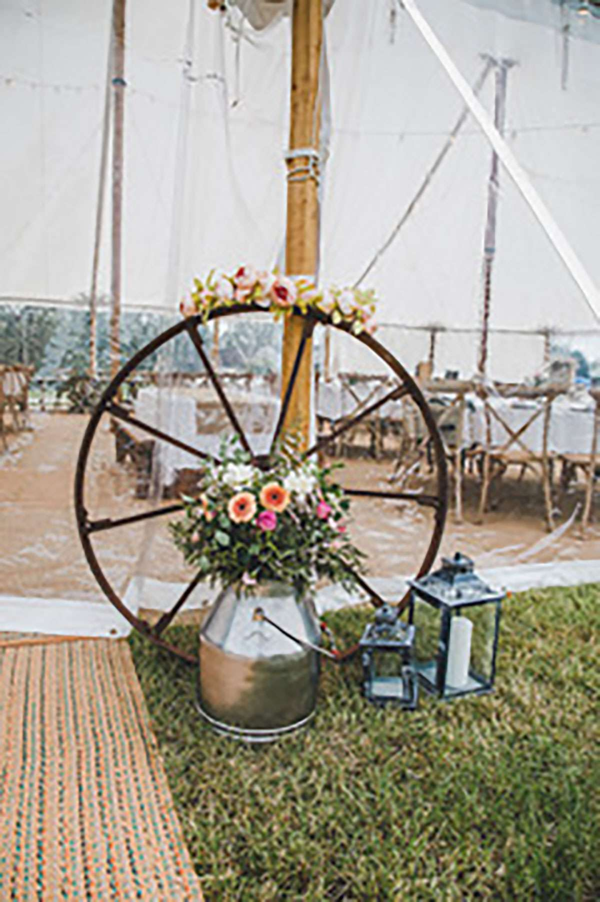 old wheel outside sailcloth tent with flowers