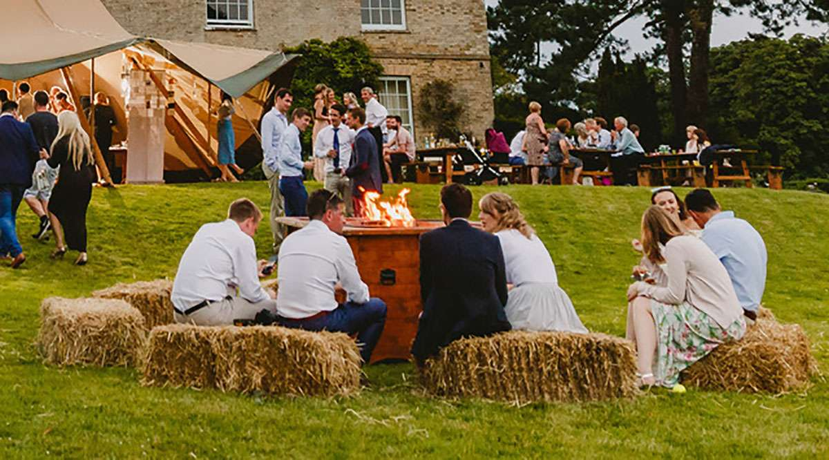 Fire pit with people sitting on hay bales outside a tipi