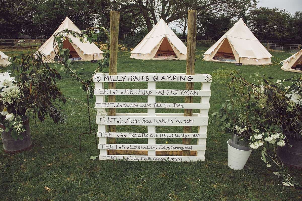 crate with text in front of glamping tents