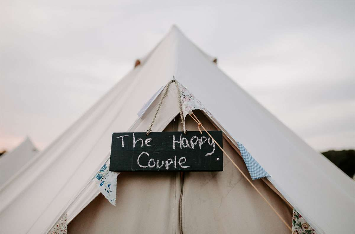 the happy couple on a blackboard on glamping tent