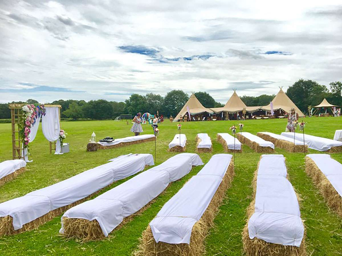 hay bales in field for tipi wedding