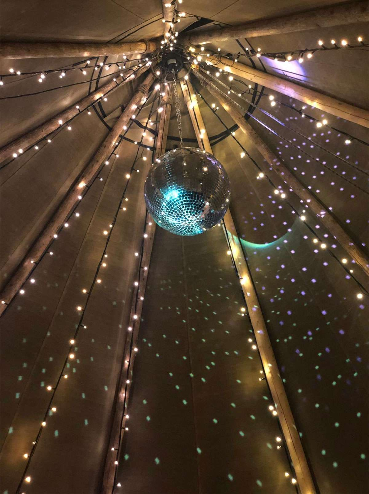 disco ball inside tipi with fairy lights on poles