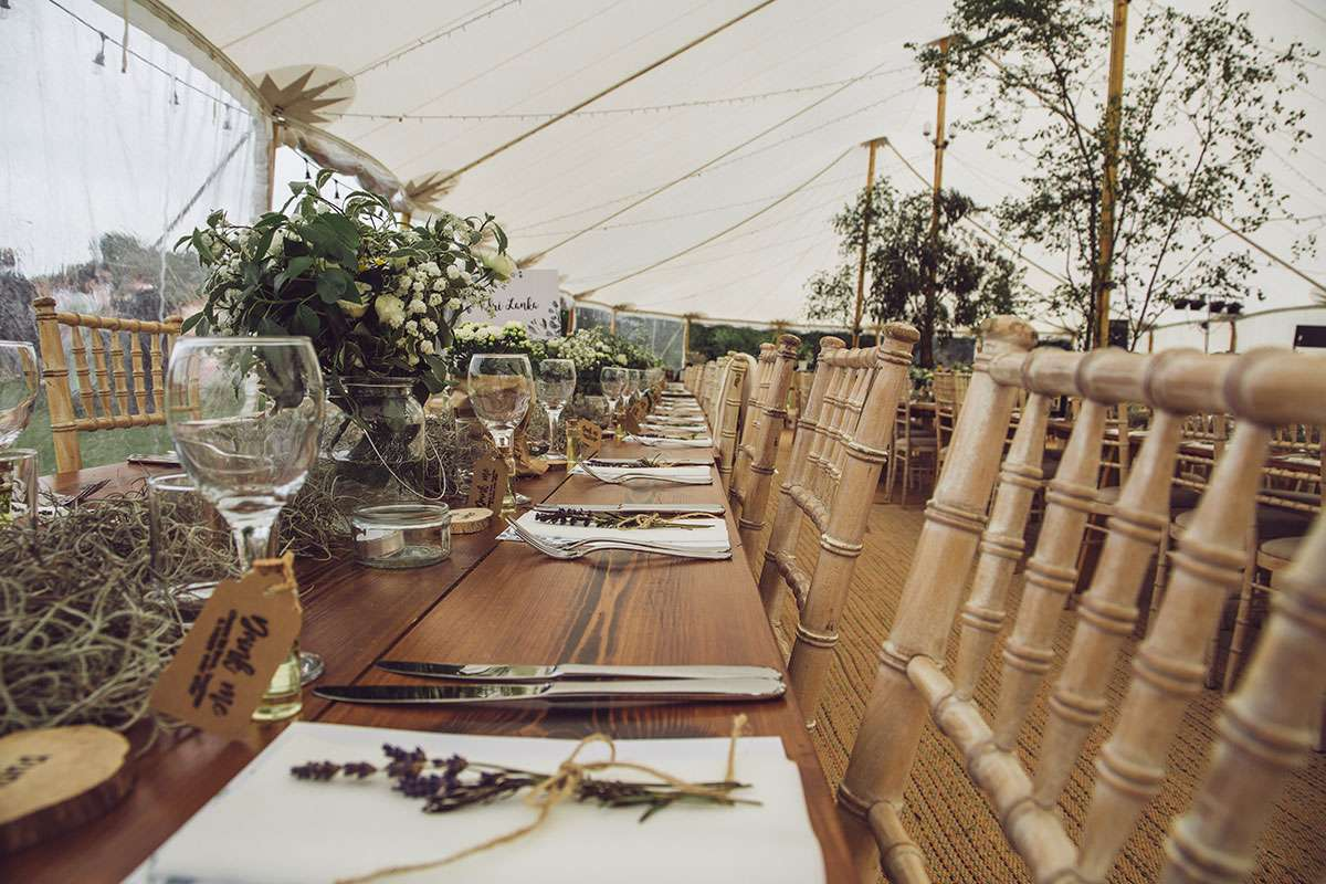 rustic tables and chairs inside sailcloth tent