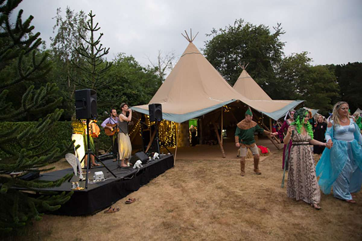 stage outside on field next to tipi