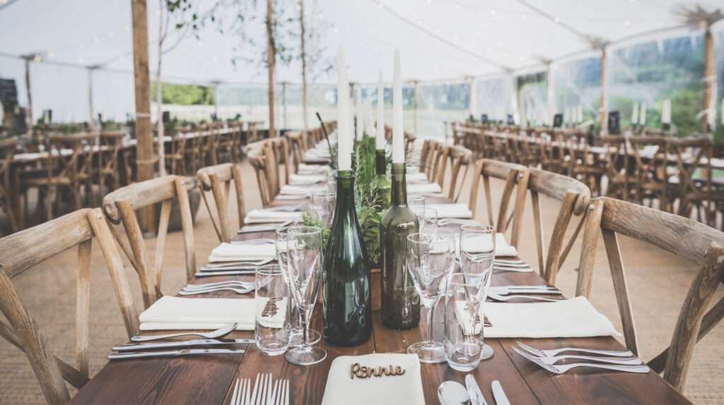 Dressed tables under a sailcloth tent